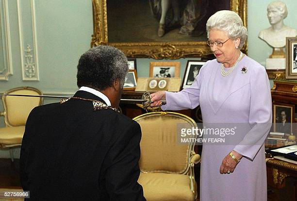 Queen Elizabeth II invests GovernerGeneral of the Solomon Islands Sir Nathaniel Waena as a Knight Grand Cross of the Order of St Michael and St...