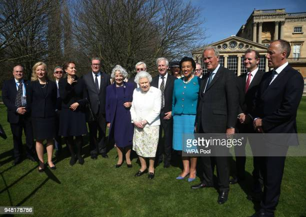 Queen Elizabeth II is accompanied by Baroness Scotland Secretary General of the Commonwealth Hugo Vickers and guests during the unveiling of a panel...