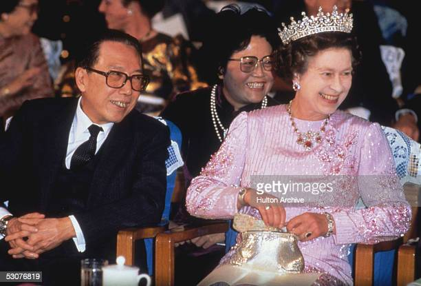 Queen Elizabeth II is accompanied by Foreign Minister Wu Xueqian to a state reception in Peking during her visit to China October 1986