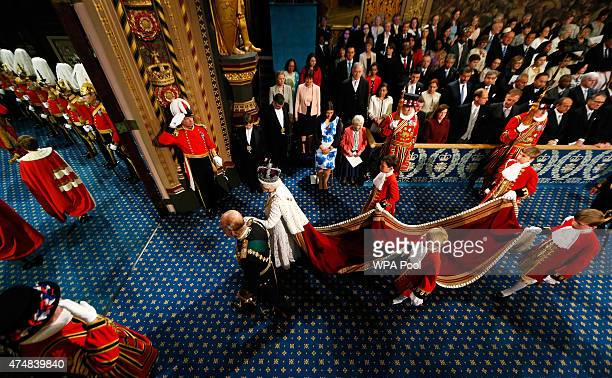 Queen Elizabeth II is accompanied by Prince Philip Duke of Edinburgh as they proceed through the Royal Gallery before the State Opening of Parliament...