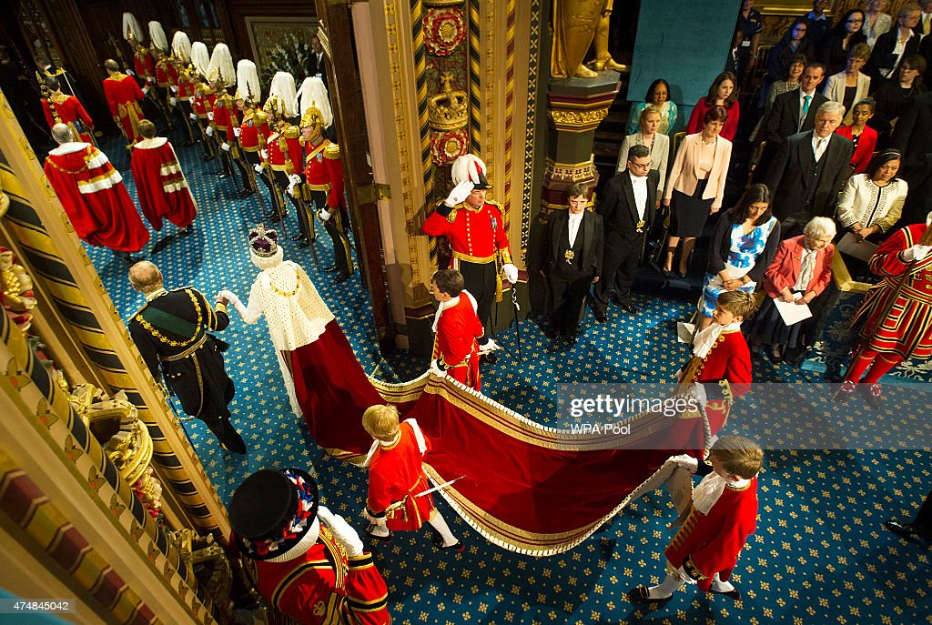 Queen Elizabeth II is accompanied by Prince Philip, Duke of Edinburgh, followed by Prince Charles and his wife Camilla, Duchess of Cornwall, pass through the Royal Gallery during the State Opening of Parliament in the House of Lords, at the Palace of Westminster on May 27, 2015 in London, England.