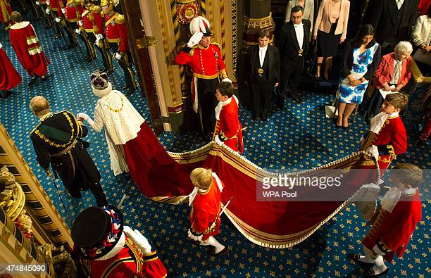 Queen Elizabeth II is accompanied by Prince Philip Duke of Edinburgh pass through the Royal Gallery during the State Opening of Parliament in the...
