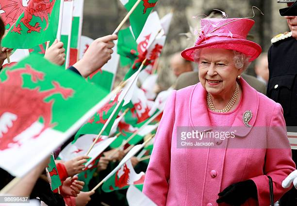 Queen Elizabeth II is cheered by school children with flags as she arrives at Caernarfon Castle on April 27, 2010 in Caernarfon, Wales. The Queen and...