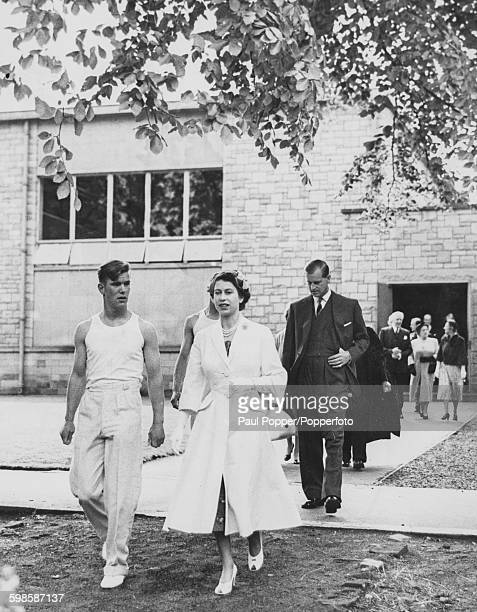 Queen Elizabeth II is escorted by prefect Donald Macbean and followed by Prince Philip Duke of Edinburgh as they make their way to the swimming pool...