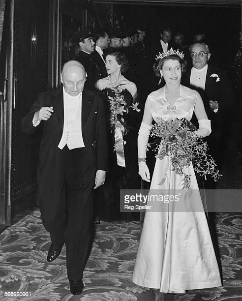 Queen Elizabeth II is escorted by Reginald Bromhead the Chairman of the Cinematograph and Trade Benevolent Fund as she and Princess Margaret leave...