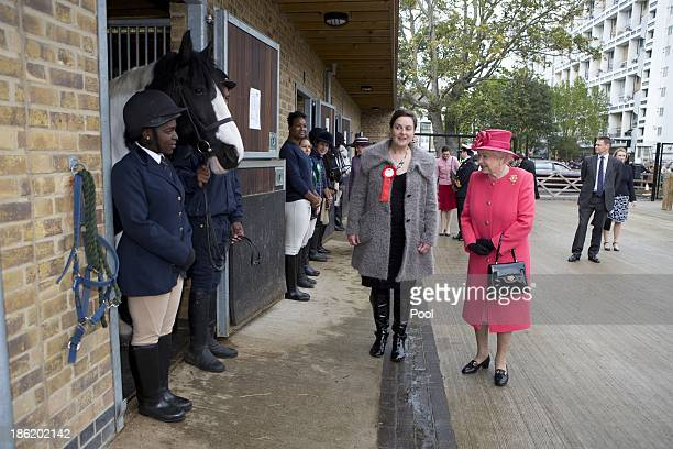 Queen Elizabeth II is given a tour by Miss Ros Spearing Director of Ebony Horse Club Community Riding Centre during an official visit on October 29...