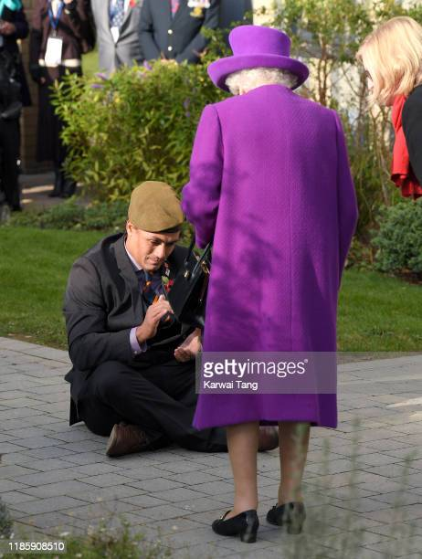 Queen Elizabeth II is given a traditional Fijian welcome by gardener and veteran John Ahben as she arrives at the Royal British Legion Industries...