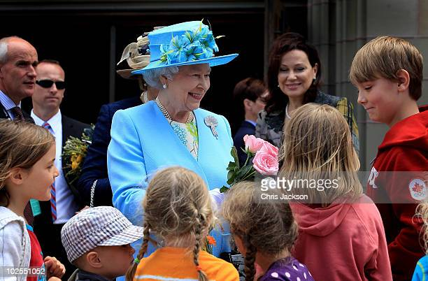 Queen Elizabeth II is given flowers by children as she visits the Canadian Museum of Nature on June 30 2010 in Ottawa Canada The Queen and Duke of...