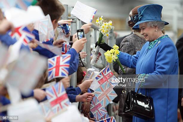 Queen Elizabeth II is given flowers by school children during her visit to Welshpool Livestock Market on April 28 2010 in Welshpool Wales The Queen...