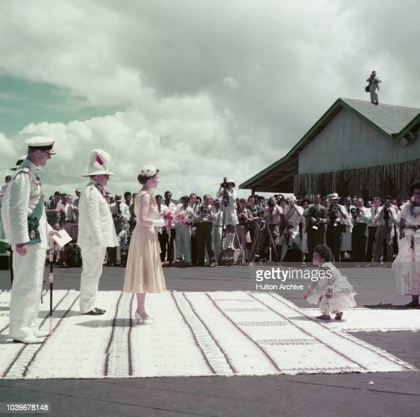 Queen Elizabeth II is greeted by a young girl at an official welcome at a quayside in Fiji during the coronation world tour December 1953 Behind the...
