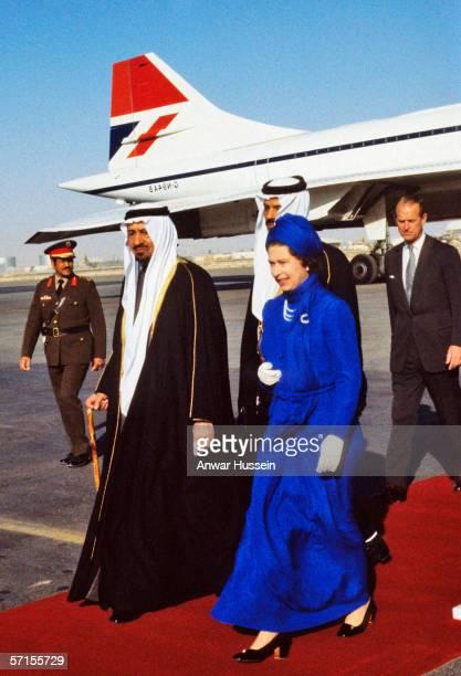 Queen Elizabeth II is greeted by King Khalid when she arrives in Saudi Arabia wearing a long dress to respect the Saudi Arabian customs during her...