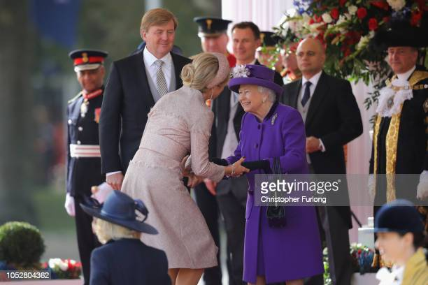 Queen Elizabeth II is greeted by Queen Maxima of the Netherlands as King WillemAlexander looks on during a ceremonial welcome at Horse Guards Parade...