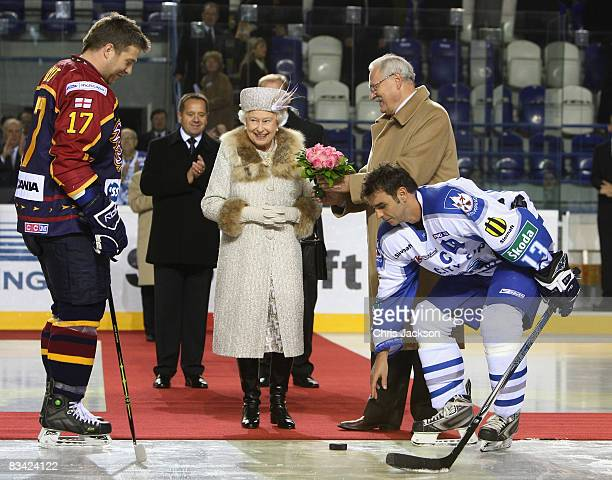 Queen Elizabeth II is handed a puck by President of Slovakia Ivan Gasparovic before throwing in the puck to start an ice hockey match between Aqua...
