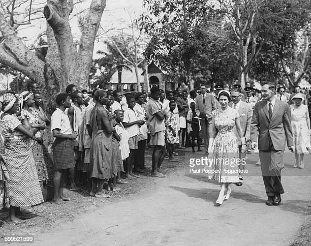 Queen Elizabeth II is led through the grounds of a leper settlement at Oji river near Enugu during a State Visit to eastern Nigeria in February 1956