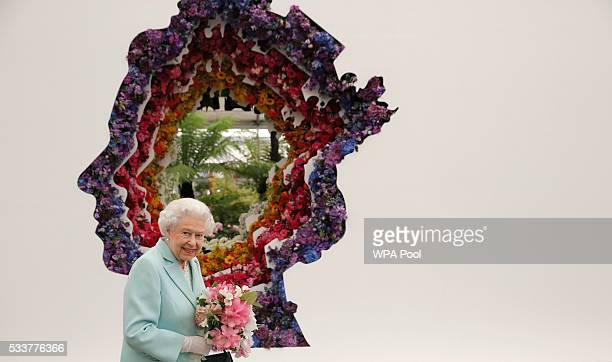 Queen Elizabeth II is pictured next to a floral exhibit by the New Covent Garden Flower Market which features an image of the Queen at Chelsea Flower...