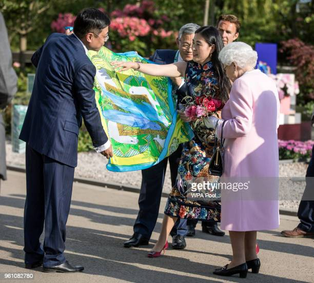 Queen Elizabeth II is presented a Chinese silk scarf depicting two whales after she looked at the Chinese show garden at the Chelsea Flower Show 2018...