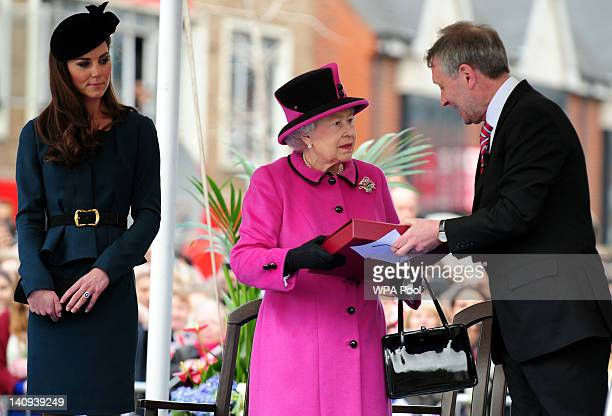 Queen Elizabeth II is presented with a book by Leicester City mayor Sir Peter Soulby during her visit to Leicester on March 8 2012 in Leicester...