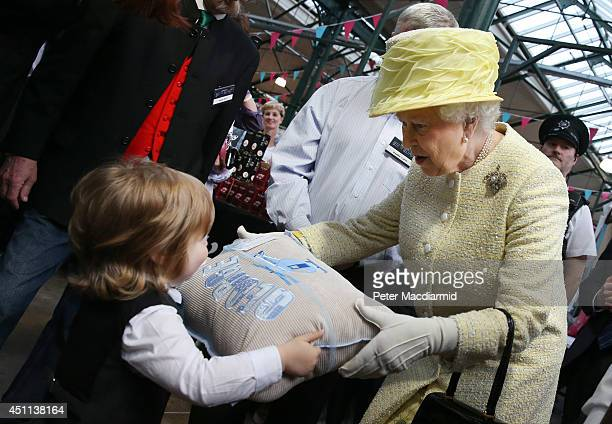 Queen Elizabeth II is presented with a cushion for Prince George by 3 year old Jack Morgan at St George's indoor market on June 24 2014 in Belfast...