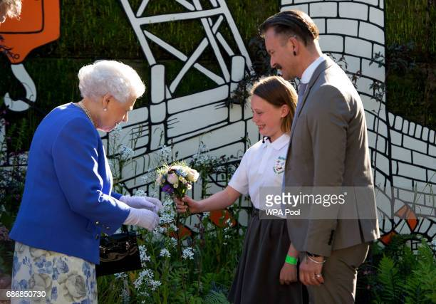 Queen Elizabeth II is presented with a posy by Caitlyn James a Y6 from Swansea during her visit to the RHS Chelsea Flower Show press day at Royal...