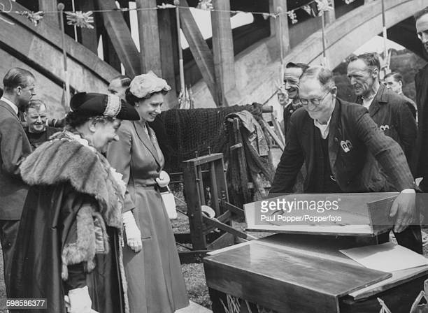 Queen Elizabeth II is presented with a salmon by the local fisherman as Prince Philip Duke of Edinburgh talks to some locals behind Her Majesty...