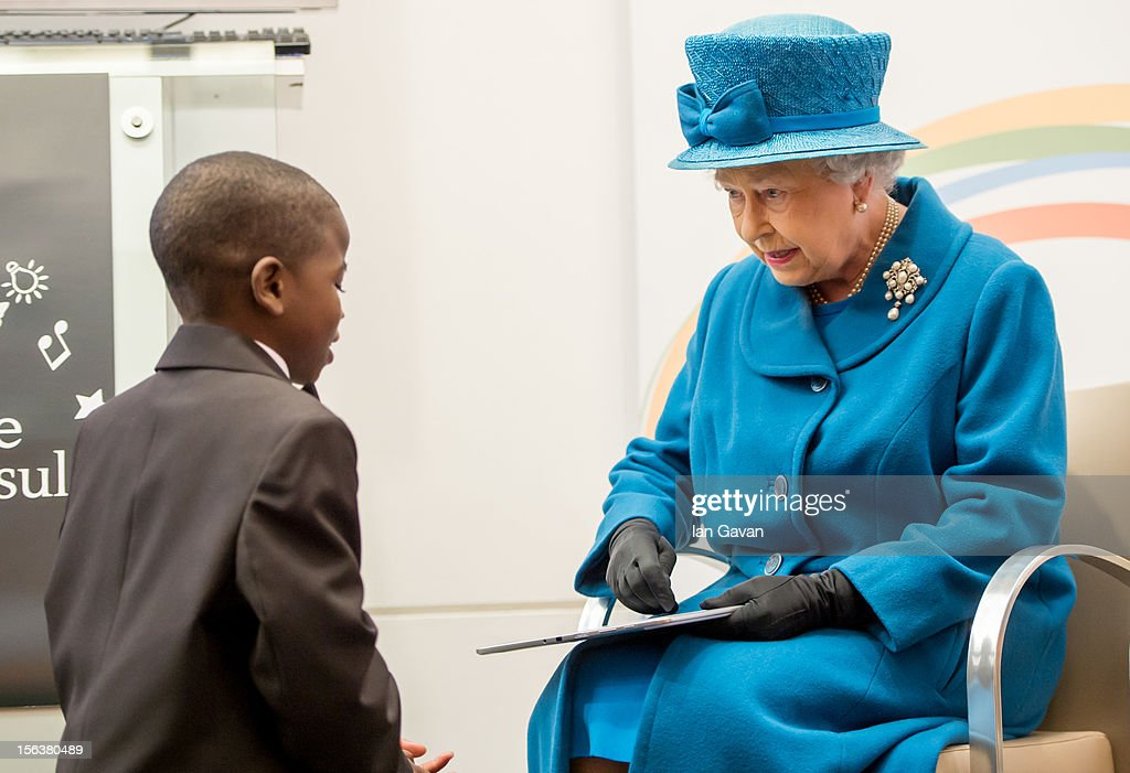 Queen Elizabeth II is presented with a tablet computer by John Samson, 12, during her visit to the Royal Commonwealth Society on November 14, 2012 in London, England.