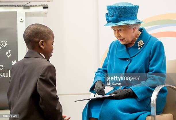 Queen Elizabeth II is presented with a tablet computer by John Samson during her visit to the Royal Commonwealth Society on November 14 2012 in...