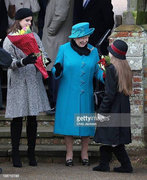 Queen Elizabeth II is presented with flowers as she leaves St Mary Magdalene Church with Princess Eugenie and other members of the royal family after...