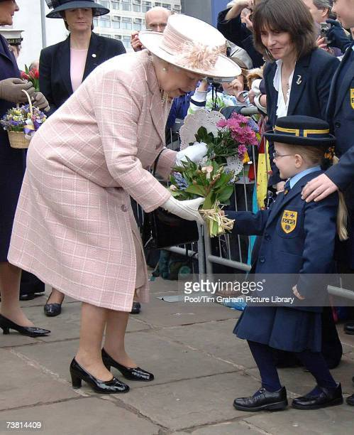 Queen Elizabeth II is presented with flowers by a young schoolgirl during a walkabout outside Manchester Cathedral after attending the traditional...