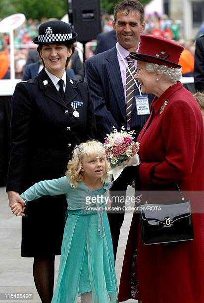 Queen Elizabeth II is presented with flowers by Lydia Beshenivsky five the daughter of murdered WPC Sharon Beshenivsky during her visit to Bradford...