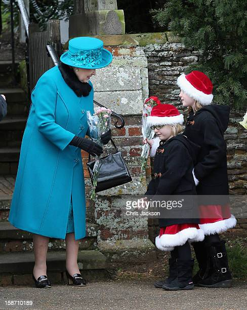 Queen Elizabeth II is presented with flowers by two girls wearing Santa outfits as she leaves St Mary Magdalene Church after attending the...