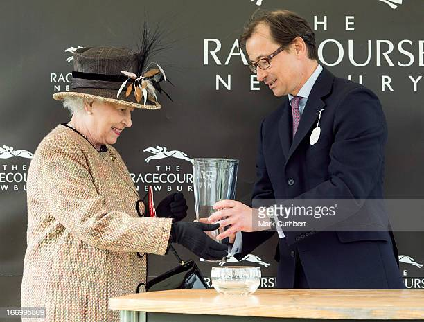 Queen Elizabeth II is presented with her trophy after her horse Sign Manual won Race 5 The Dreweatts Handicap Stakes riden by Hayley Turner at...