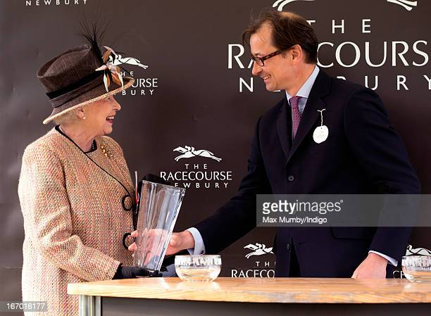Queen Elizabeth II is presented with the winning owners trophy after her horse 'Sign Manual' won the Dreweatts Handicap Stakes during the Dubai Duty...