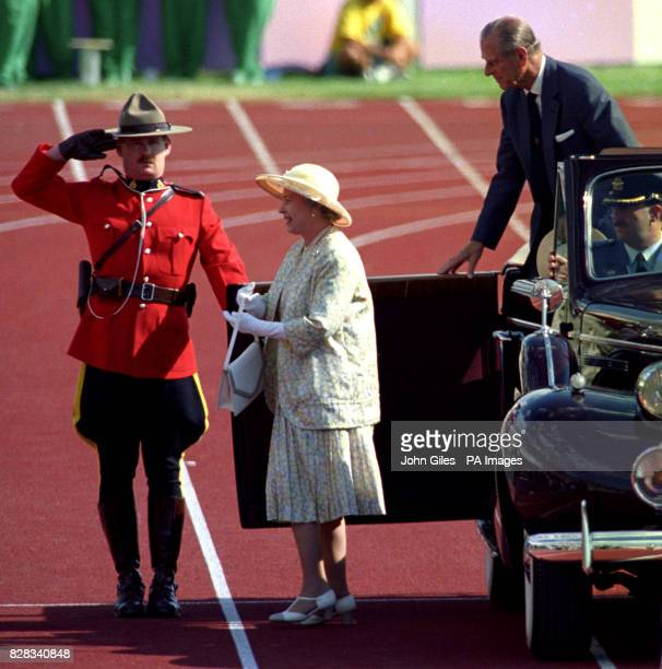 Queen Elizabeth II is saluted by a member of the Royal Canadian Mounted Police as se arrives to open the Commonwealth Games in Canada