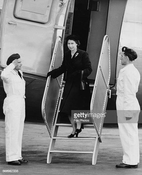 Queen Elizabeth II is saluted by the crew as she leaves her Viking airplane of the King's Flight London Airport June 3rd 1952