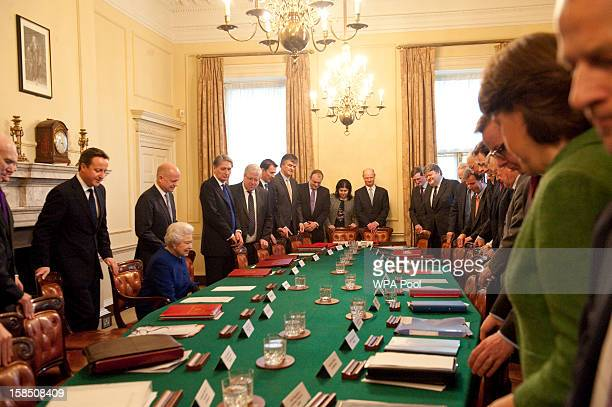 Queen Elizabeth II is seated as British Prime Minister David Cameron and other members of the cabinet look on at Number 10 Downing Street to attend...
