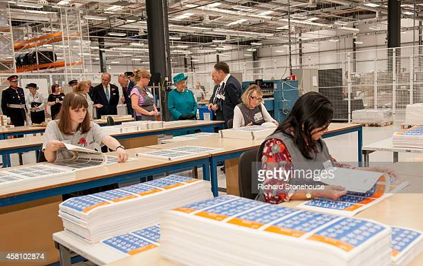 Queen Elizabeth II is show stamp quality control by MD Paul White production Manager Andrew Bannister during an official visit to International...