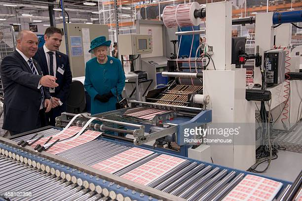 Queen Elizabeth II is shown stamp cutting and finishing machines by production manager Andrew Bannister and MD Paul White during an official visit to...