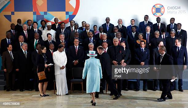 Queen Elizabeth II joins Commonwealth Heads of State as she arrives for a group photograph at CHOGM opening ceremony at the Mediterranean Conference...