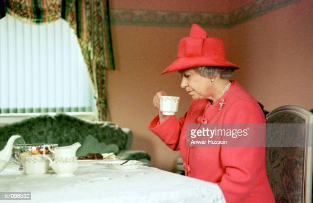 Queen Elizabeth II joins Mrs Susan McCarron her tenyearold son James and Housing Manager Liz McGinniss for tea in their home in the Castlemilk area...