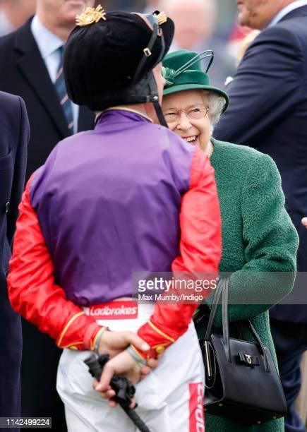 Queen Elizabeth II jokes with jockey Frankie Dettori as she attends the Dubai Duty Free Spring Trials horse racing meet at Newbury Racecourse on...