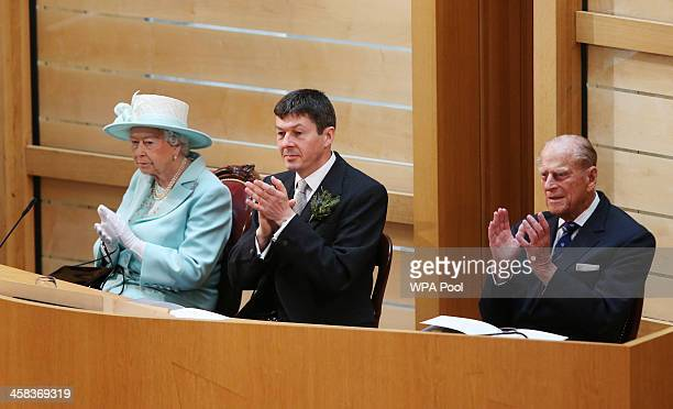 Queen Elizabeth II Ken Macintosh Presiding Officer of the Scottish Parliament and Prince Philip Duke of Edinburgh applaud during the opening of the...