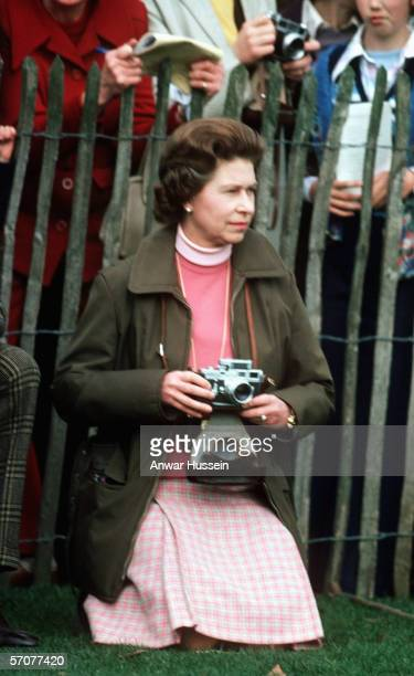 Queen Elizabeth II kneels down with a camera and watches the Badminton Horse Trials on October 14 1975 in Badminton England