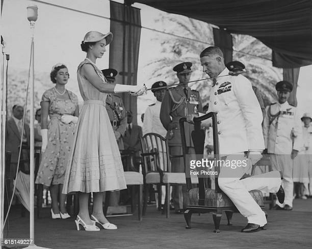 Queen Elizabeth II knighting Air Marshal Claude Pelly , Commander-in-Chief of the RAF Middle East Air Force, by touching his shoulder with a...