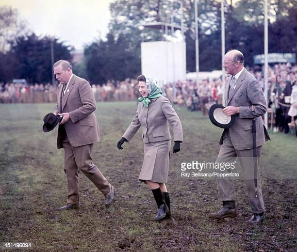 Queen Elizabeth II laughing as she walks through mud in her Wellington boots during the Royal Windsor Horse Show in Berkshire on 11th May 1968 Photo...