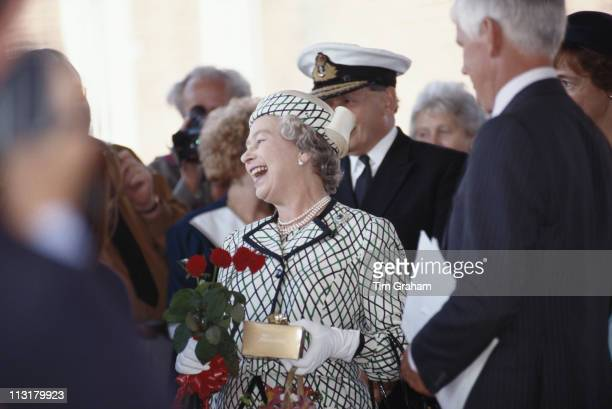Queen Elizabeth II laughing while holding a small bouquet of flowers before boarding the Royal yacht Britannia in Portsmouth Hampshire England Great...
