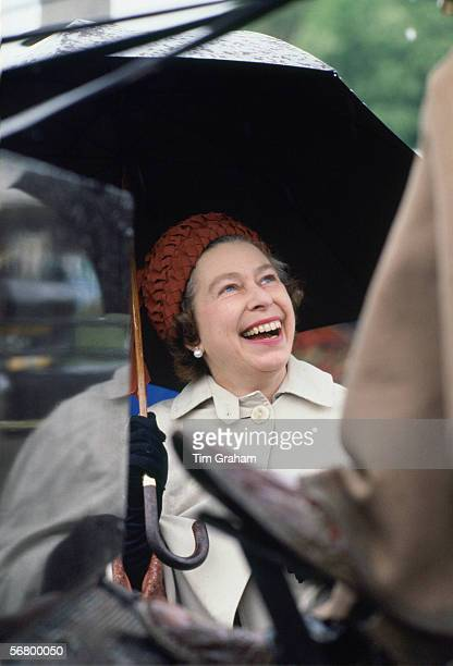 Queen Elizabeth II laughing whilst taking shelter under an umbrella at the Royal Windsor Horse Show.