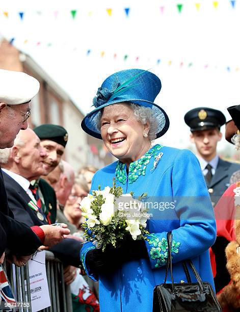 Queen Elizabeth II laughs as she meets members of the public in Welshpool town centre on April 28, 2010 in Welshpool, Wales. The Queen and Duke of...