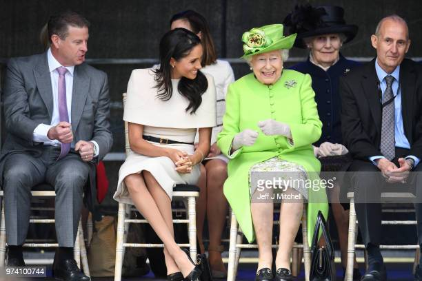 Queen Elizabeth II laughs with Meghan Duchess of Sussex during a ceremony to open the new Mersey Gateway Bridge on June 14 2018 in the town of Widnes...