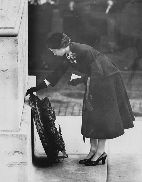 Queen Elizabeth II laying a wreath against the Cenotaph in Whitehall in front of crowds of people on Remembrance Sunday London November 7th 1954