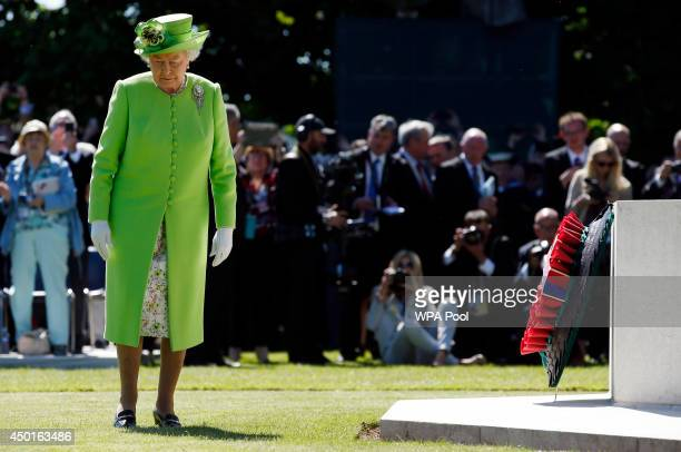 Queen Elizabeth II lays a wreath at the foot of the Cross of Sacrifice in the centre of Commonwealth War Graves Commission Cemetery during a service...